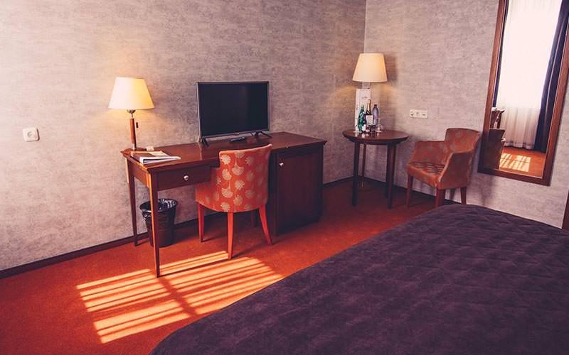 A double guest room with desk, bed, chairs, TV and lamps
