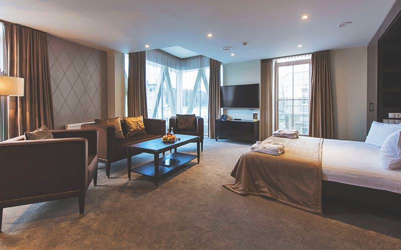 A very large guest suite with double bed and seating and dining areas