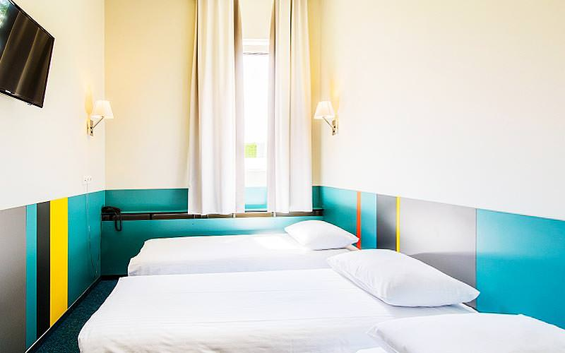 A compact, colourful guest room at Ecotel Hotel