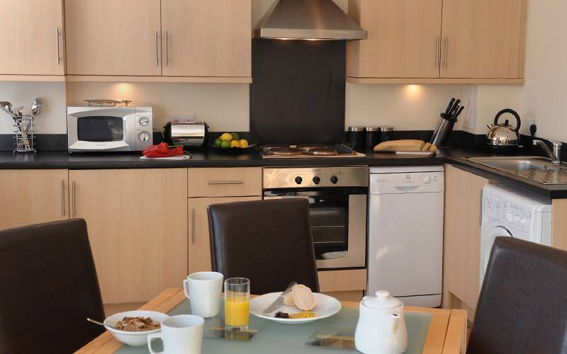 A kitchenette with a dining table and breakfast items on