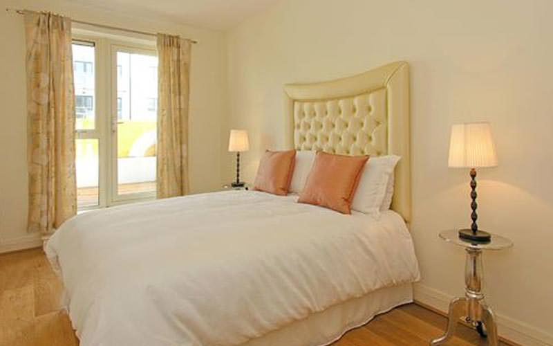 A double bed topped with two peach cushions, in a magnolia hotel room, with lamps on two tables at each side of the bed