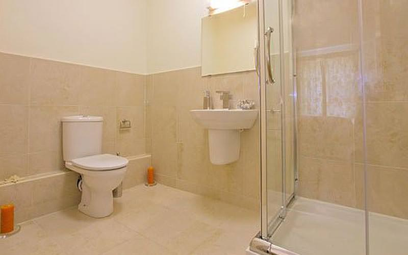 A cream tiled bathroom, featuring a toilet, sink and glass shower