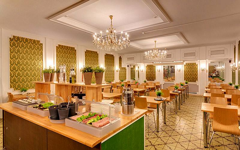 The dining area and breakfast buffet, with tables, chairs and chandeliers.