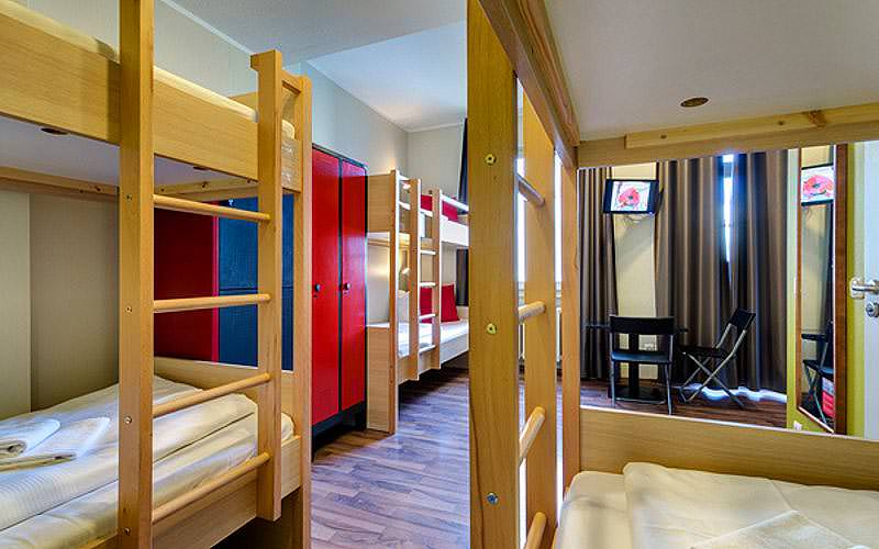 A large guest room at containing lockers, TVS and wooden bunk beds