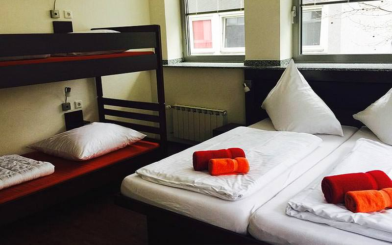 A room containing a bunk bed and a set of twin beds