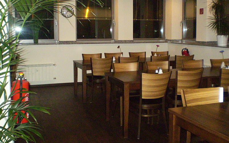 A dining area with wooden chairs, tables and plants