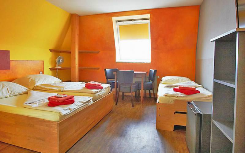 A guest room with three beds and orange and yellow sloped walls
