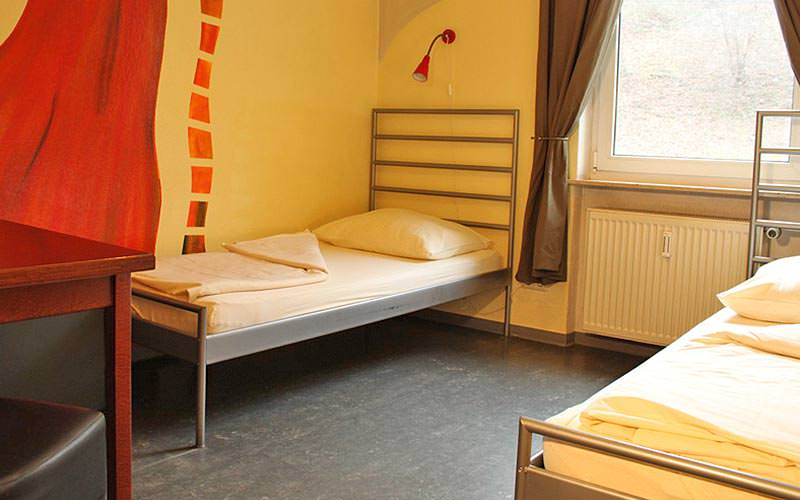A guest room with twin beds, yellow walls and a grey floor