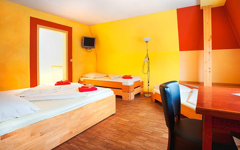 A large guest room with three beds, a desk and yellow walls