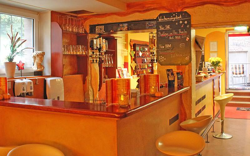 A small hostel bar with bar stools and yellow walls