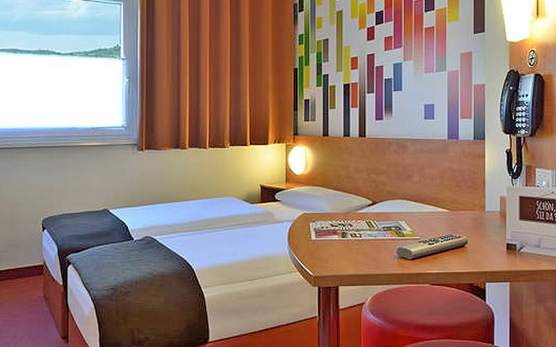 A twin guest room with a multicoloured wall, table and phone