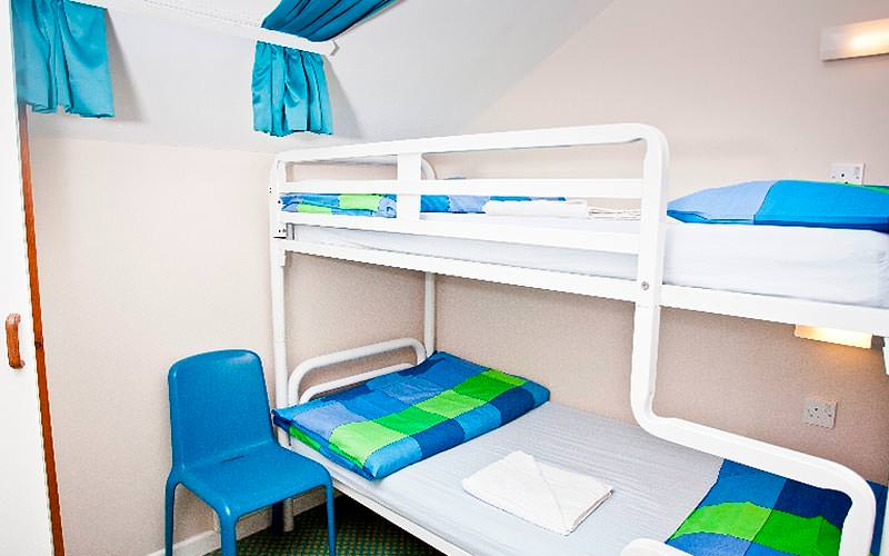 White bunk beds topped with blue and green blankets, next to a blue chair