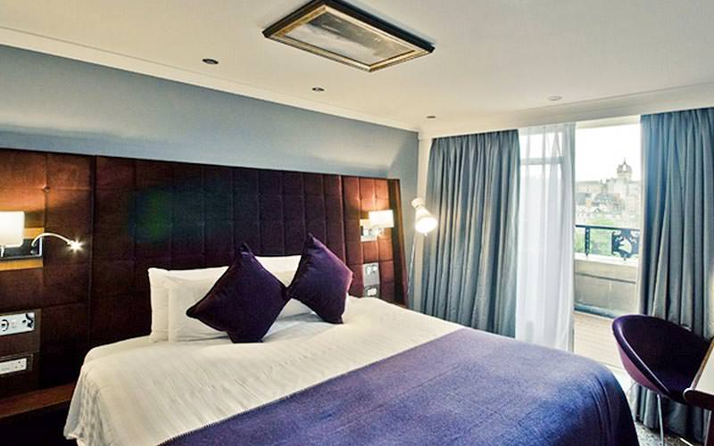 A double bed with a purple throw and cushions, in a hotel room