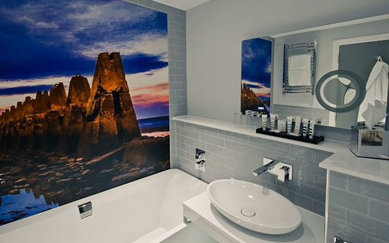 A panoramic picture on the wall of a grey tiled bathroom