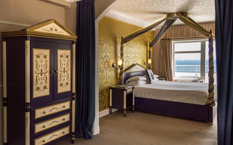 A four poster bed in a large room, with an antique looking wardrobe