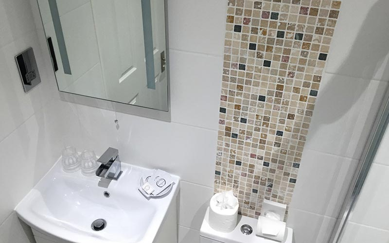 A white tiled bathroom area