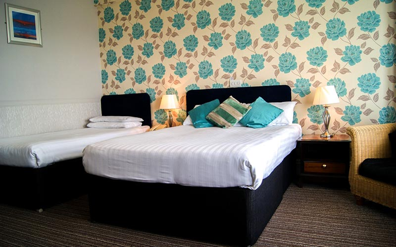 A single and a double bed in a room with old fashioned flowery wallpaper