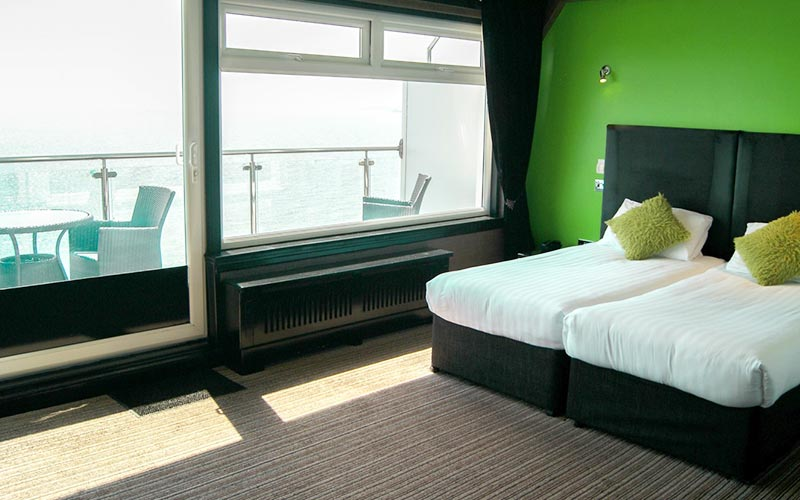 A twin room with green walls and a picturesque sea view