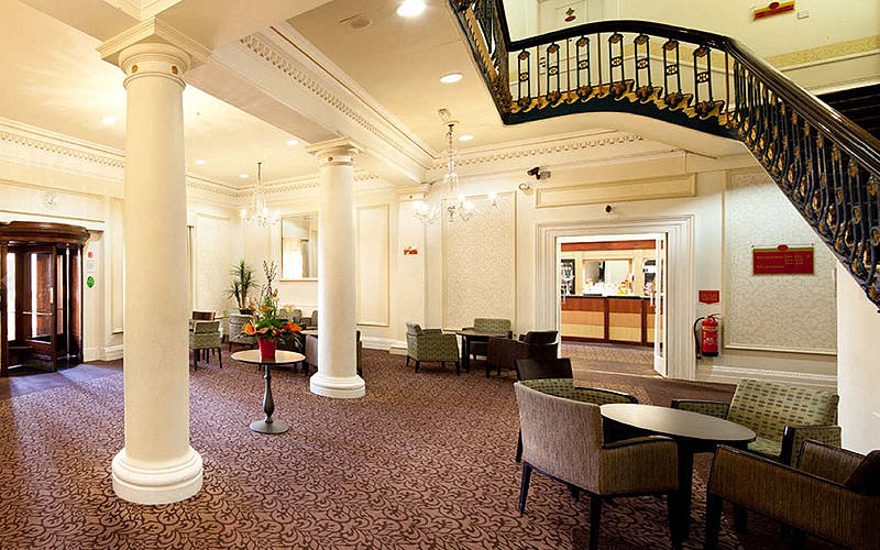 The grand hotel lobby of the Mercure Seafront, Brighton, with a sweeping staircase along the right side