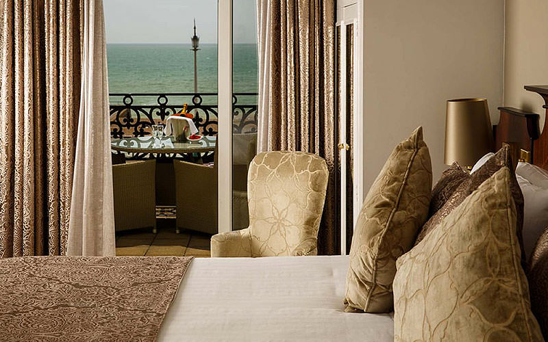 A double bed in a hotel room, with a balcony overlooking the sea in the background