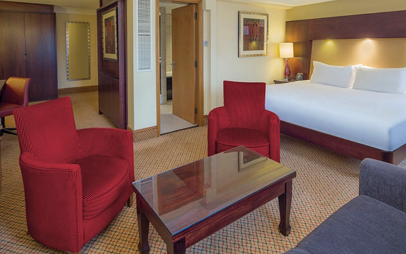 Two red chairs and a coffee table, with a double bed and cupboards in the background in a hotel room