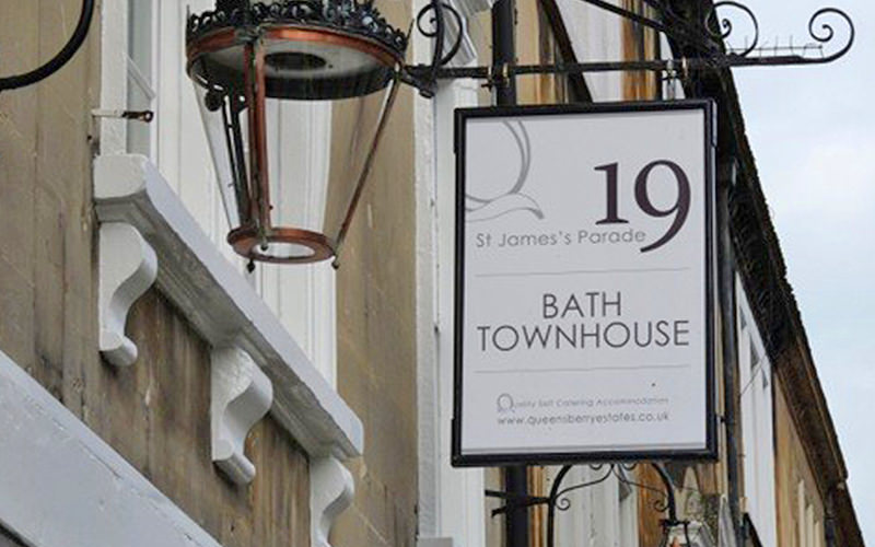 The exterior of Bath Townhouse with a sign outside