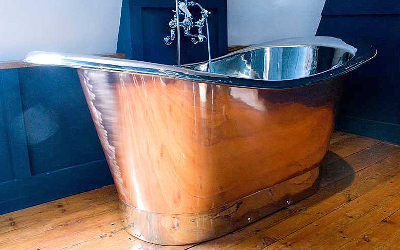 A vintage tin bath on a wooden floor