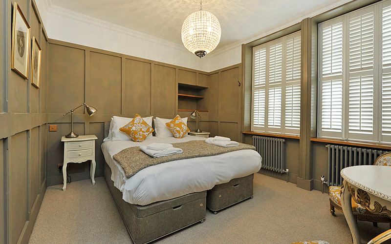 A grey and cream room with a double bed and large windows with blinds