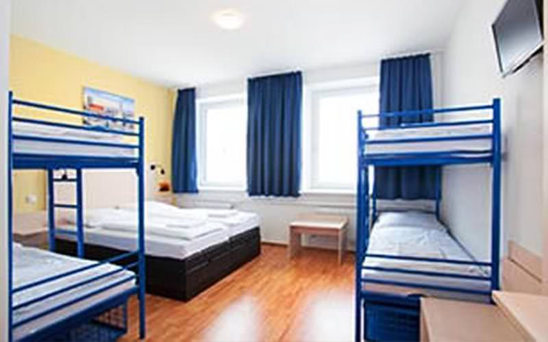 Inside a dormitory room, with two blue bunk beds and a double bed