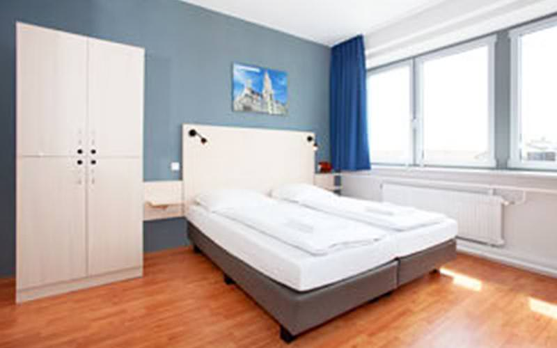 A spacious double bedroom with a white wardrobe, and three windows on the back wall