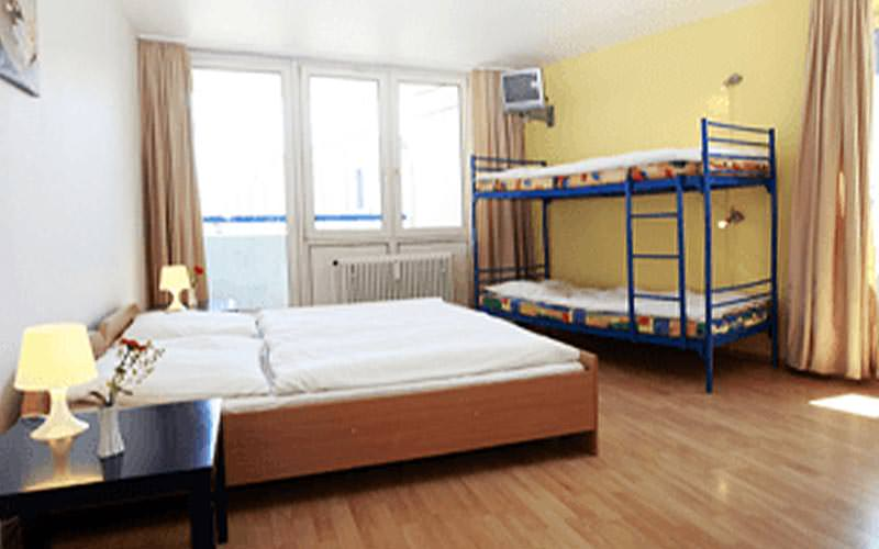 A double bed and a bunk bed within a room in A&O Hackerbruke
