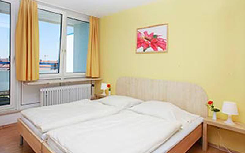 A double room with lemon yellow walls and a picturesque view