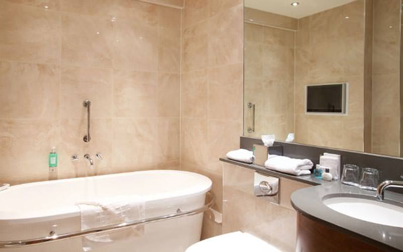 A bath, sink with large mirror above in a cream tiled bathroom
