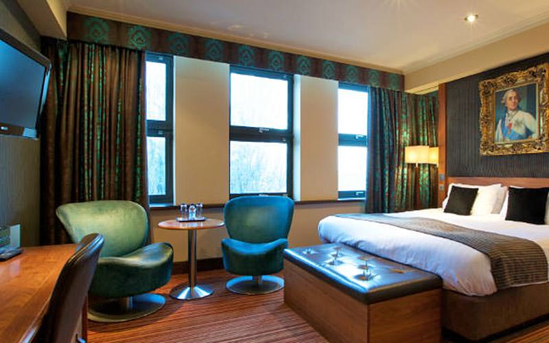 A double bed in a blue and green hotel room, with a picture above the bed and chairs in the corner, facing a desk