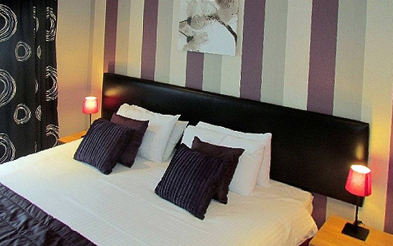 A double room with striped wallpaper and black, white and purple bedding