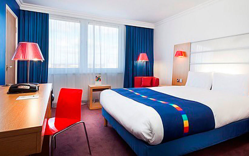 A spacious double room with white bedding, a blue runner on the bed and a red chair next to the desk