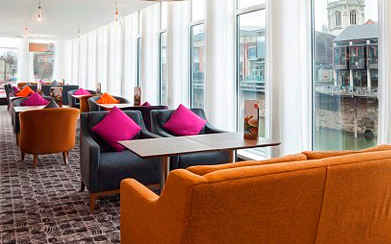 Orange and grey sofas next to huge windows showing the river views