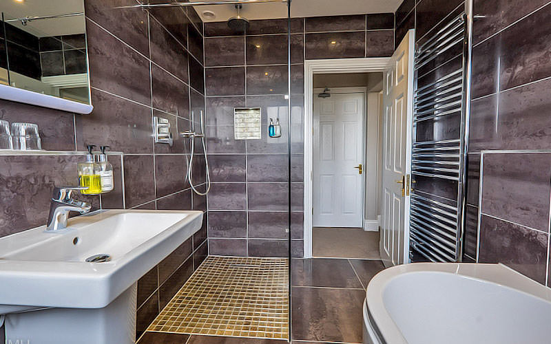 Grey tiled bathroom, featuring a walk-in shower, and sink and bath in the foreground