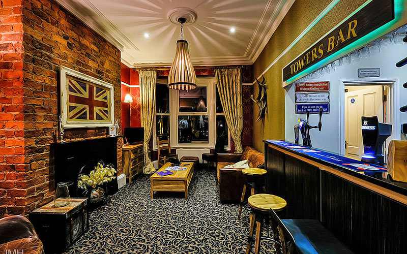 The Towers Bar at Hedley House Hotel, with exposed brick, bar stools and wooden coffee tables