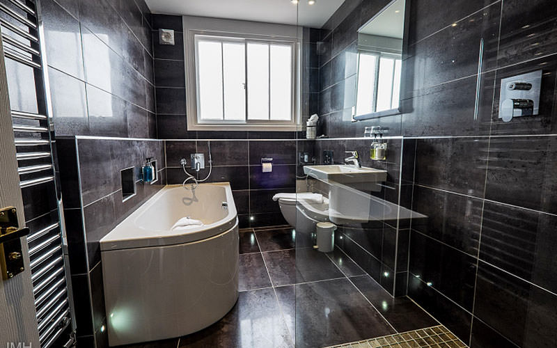 Grey tiled bathroom with a walk-in shower in the foreground, and a bath, toilet and sink in the back
