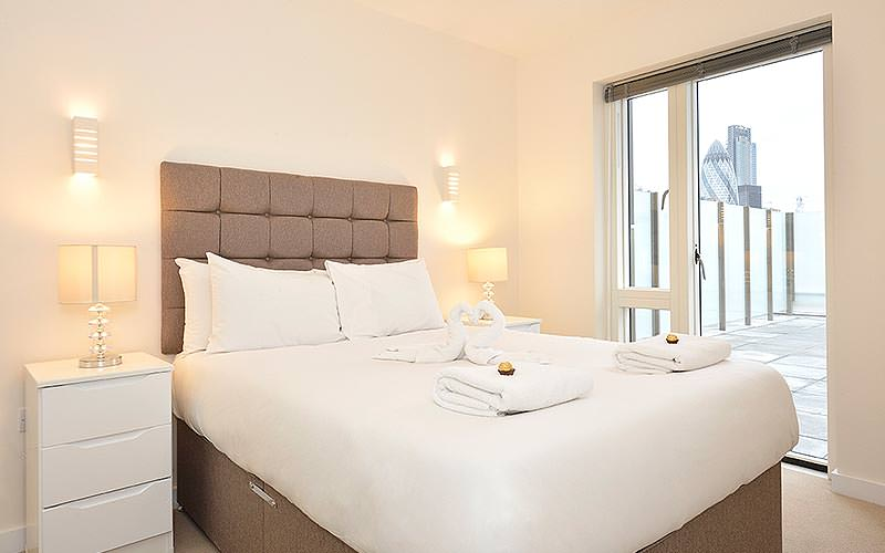 A double room with towels on the end of the bed with Ferrero Rochers on the top