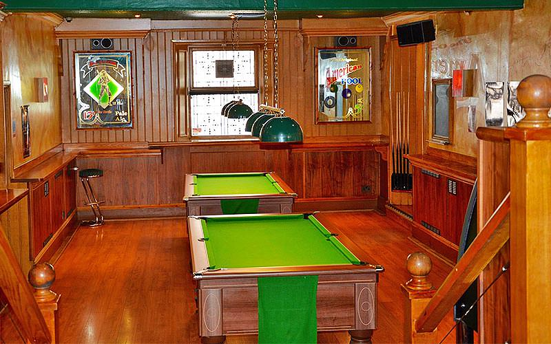 Two pool tables in the middle of a wooden-style room