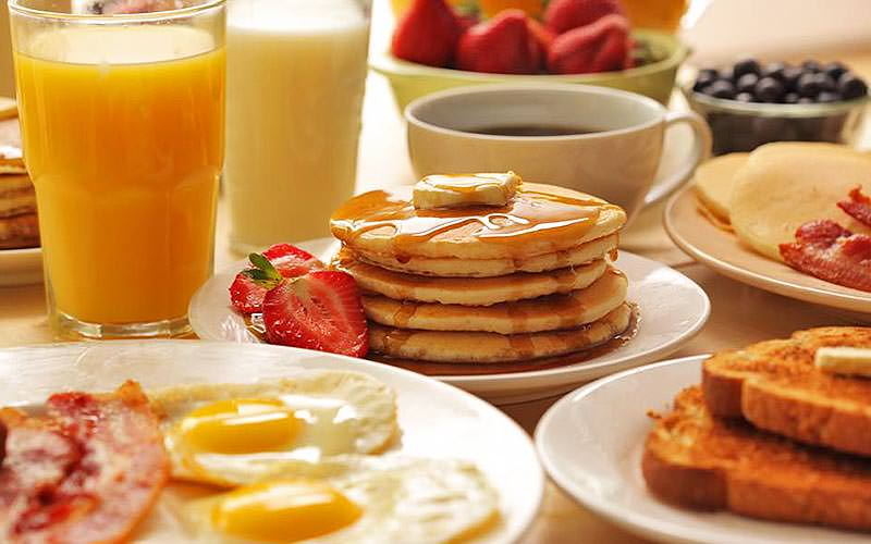 Pancakes, fries breakfast and various other dishes alongside orange juice and coffee on a table