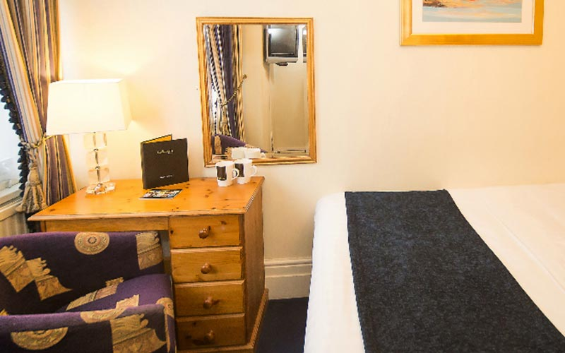 A double bed in a hotel room at Hallmark Chester Inn, facing a set of drawers and a table