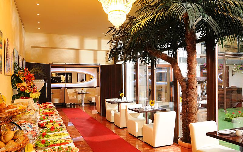 The breakfast buffet area with plush seating and an indoor palm tree