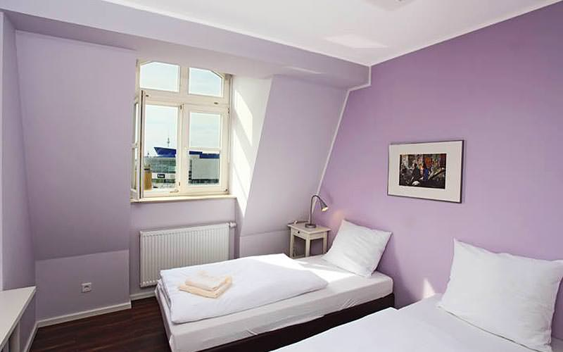 A lilac room with two single beds in and a large window open
