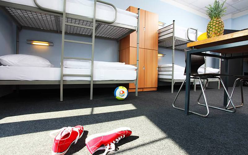 A dormatory bedroom with bunk beds, desks, wardrobes, and some red trainers in the foreground