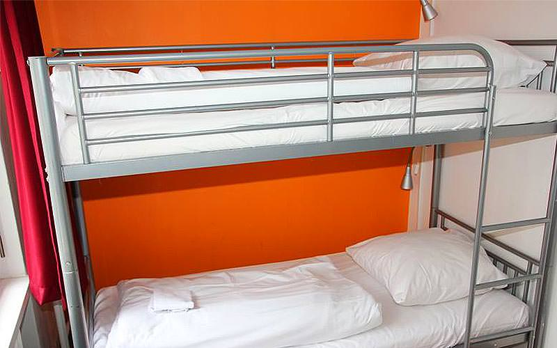 A bunkbed against an orange wall