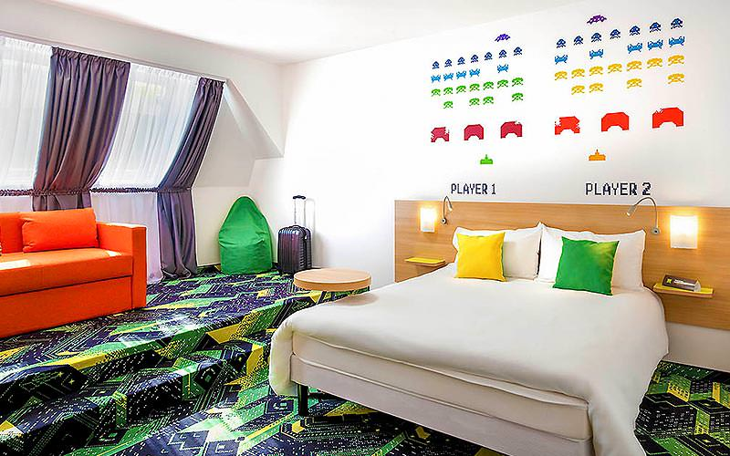 A white double bed with an orange sofa and green beanbag in the background, in a room with a vibrant green carpet and Space Invader stencils on the wall