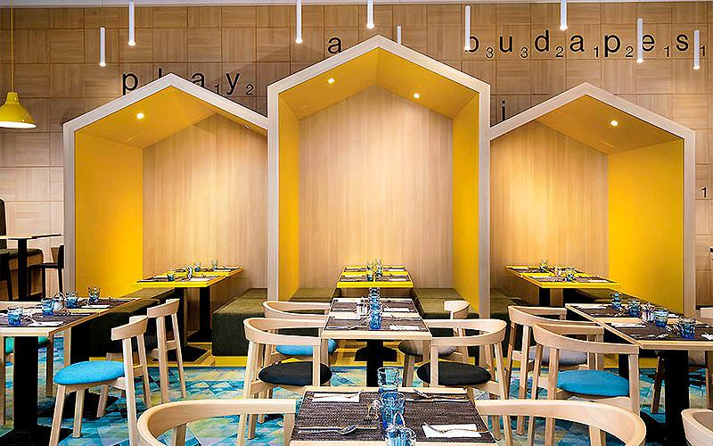 Three yellow arches above tables and chairs set for dinner, in the hotel restaurant at Ibis Styles Hotel